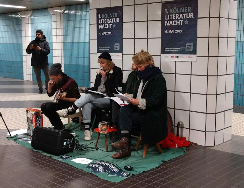 Das Ensemble Klub Bronko bei der Performance in der Zwischenebene der KVB am Rudolfplatz. Sie werden begleitet vom Musiker Dr. Nikolai Blau